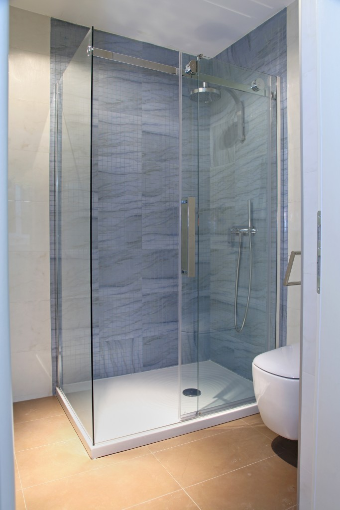 Modern shower with glass cabin inside bathroom interior